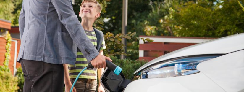 Father and son plugging in an electric car